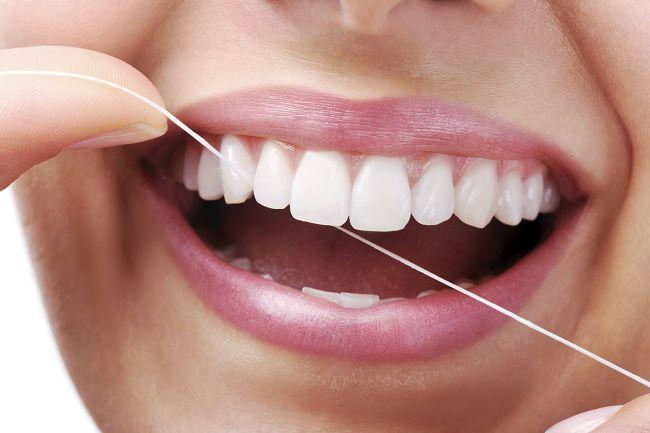 Девушка пользуется зубной нитью