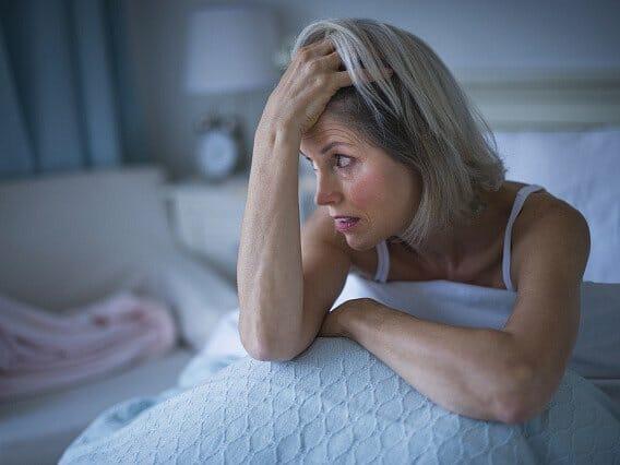 Женщина сидит на кровати ночью