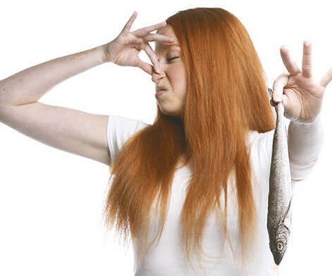 Девушка закрыла нос от запаха рыбы