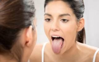 Девушка осматривает язык в зеркале