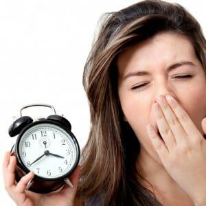 Девушка с будильником зевает
